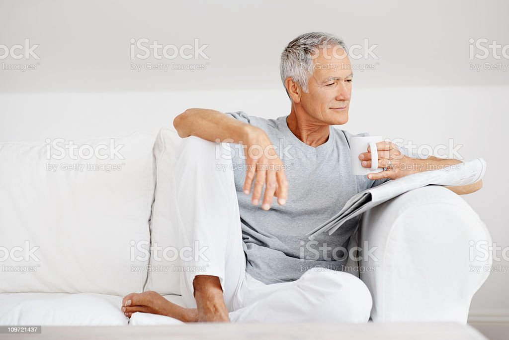 Senior man reading newspaper with coffee cup in hand royalty-free stock photo