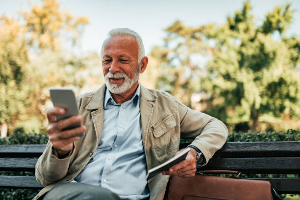 Senior man reading online news on smartphone outdoors. stock photo