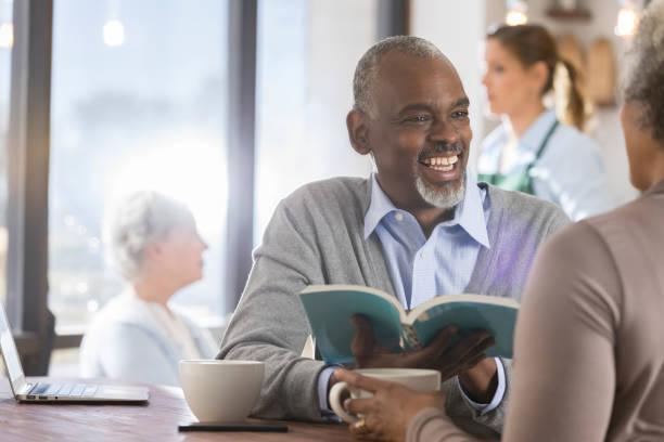 ältere mann liest buch mit frau - gedichte zum ruhestand stock-fotos und bilder