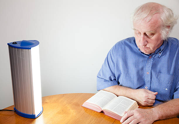 senior man reads by seasonal affective disorder SAD lamp senior man reads by seasonal affective disorder SAD lamp - these lamps simulate strong daylight and are believed to be effective i controlling  depression associated with lack of daylight in winter months -