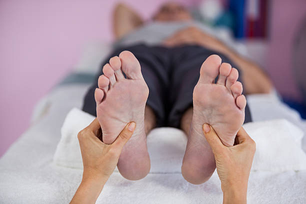 senior man receiving foot massage from physiotherapist - old man feet stock photos and pictures