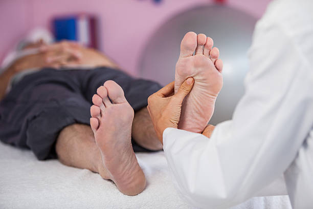 Senior man receiving foot massage from physiotherapist stock photo