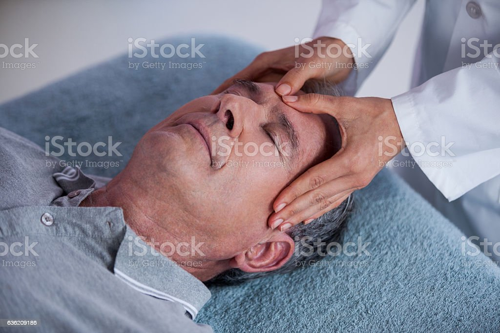 Senior man receiving head massage from physiotherapist stock photo