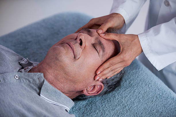 Senior man receiving head massage from physiotherapist stock photo