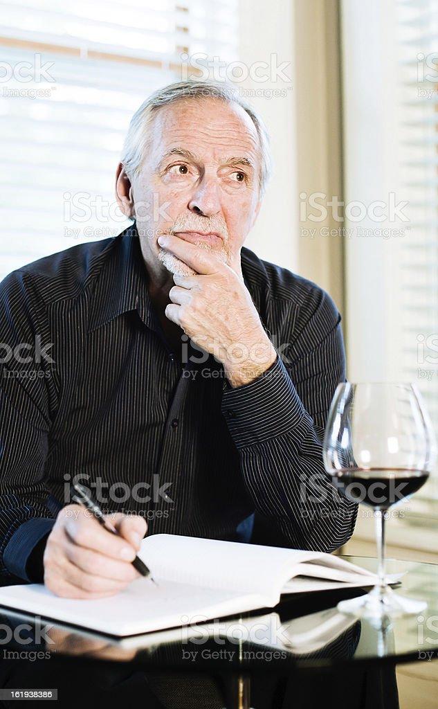 Senior man reflecting while writing royalty-free stock photo