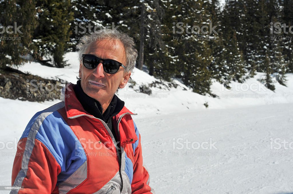 Senior man relaxing after heavy skiing with sunglasses royalty-free stock photo
