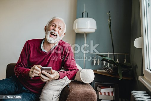 Senior men in a red sweater sitting on a sofa in the living room and holding smart phone