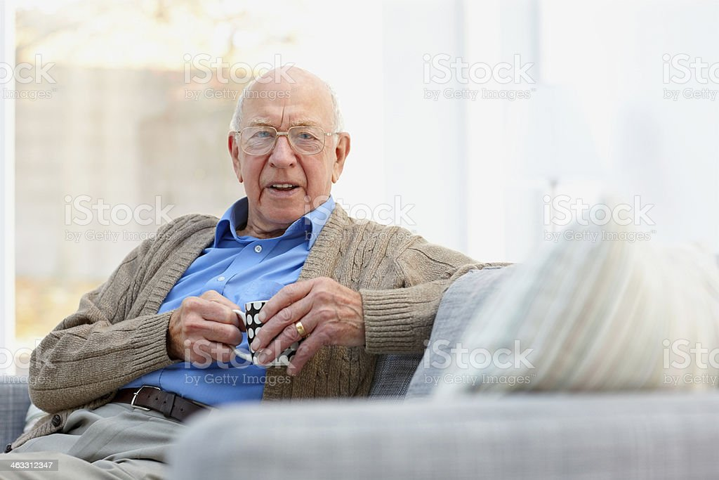 Senior man relaxing at home with a cup of coffee stock photo