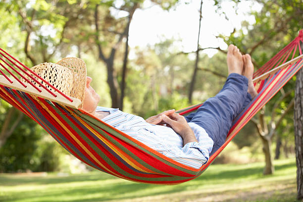 senior man relaxing in hammock - hangmat stockfoto's en -beelden