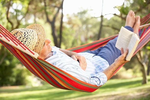 uomo anziano rilassante amaca con libro in - amaca foto e immagini stock