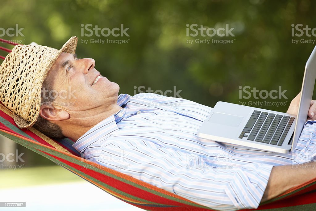 Senior Man Relaxing In Hammock With Laptop stock photo