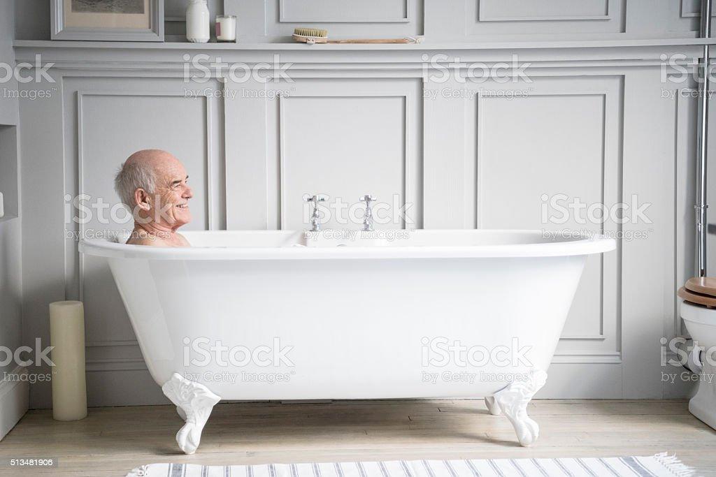 Uomo anziano rilassante nella vasca da bagno bianco sorridente