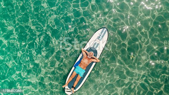 Photo of a senior man relaxing on a paddleboard in the sea