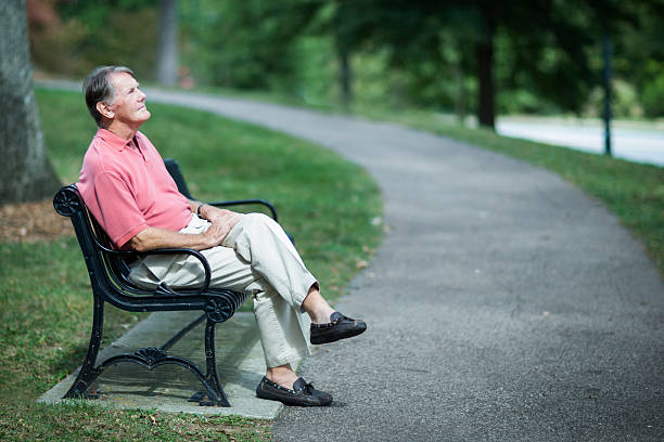 Senior Man Relaxing On Park Bench. stock photo