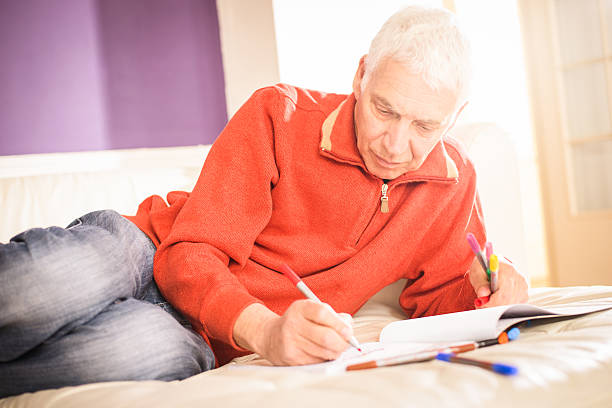 Senior Man Relaxing with Adult Colouring Book stock photo