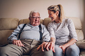 The senior man sits on the sofa in his living room beside his daughter. The woman smiles at her father with her hand resting on his.