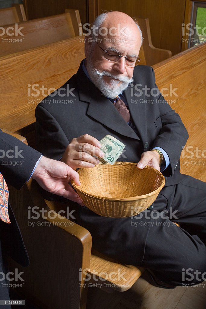 Senior Man Reluctantly Putting Money into Church Offering Basket stock photo