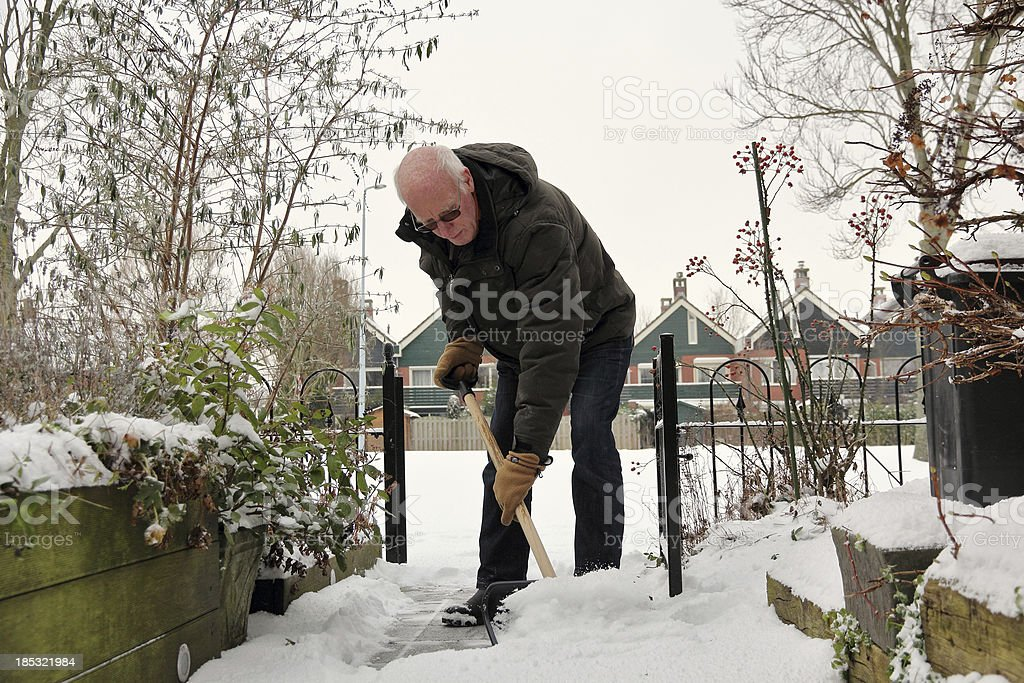 Senior man removes snow stock photo
