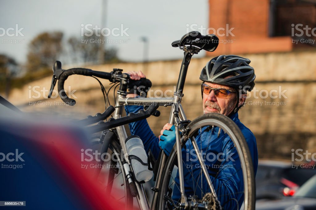 Senior Man removing Cycle from Bike Rack stock photo