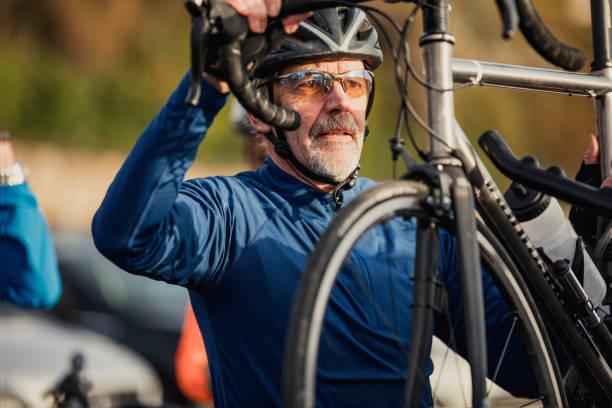 senior-mann entfernen zyklus von fahrradträger - fahrradhalter stock-fotos und bilder