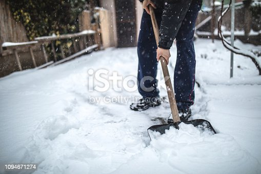 Senior man with a shovel cleaning snow from his back yard at his house.
