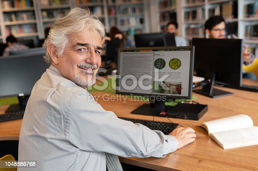 Senior man researching online using computer at a library and looking at the camera smiling - education concepts. **DESIGN ON SCREEN WAS MADE FROM SCRATCH BY US**