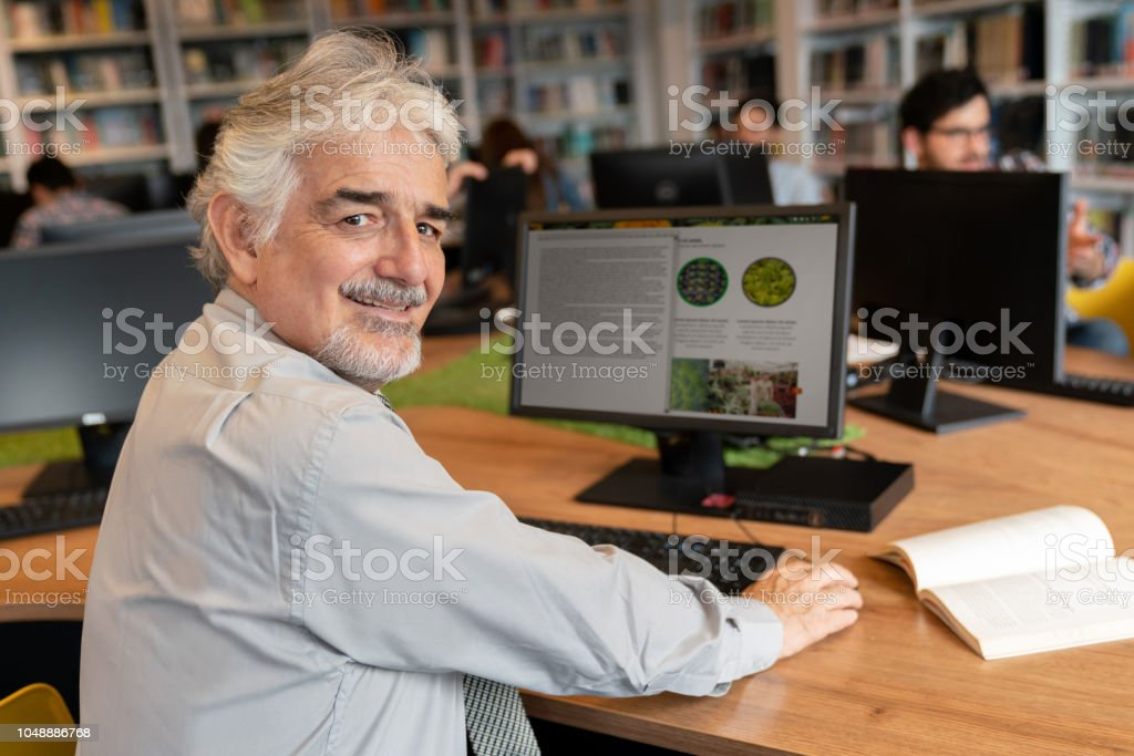 Senior man researching online at a library stock photo