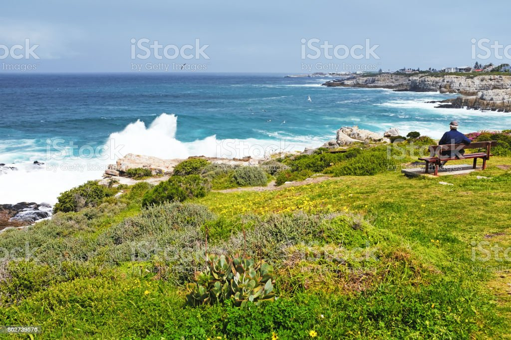 Senior man resting on a bench near the Atlantic Ocean  in Hermanus,South Africa stock photo