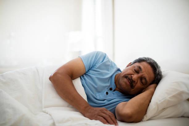 Senior man resting on bed in bedroom stock photo