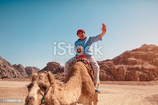 883177796istockphoto Senior man rides a camel in desert by Sinai mountains. Happy tourist waving at camera 1128990193