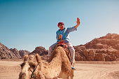 Senior man rides a camel in desert by Sinai mountains. Happy tourist waving at camera. Vacation in Egypt