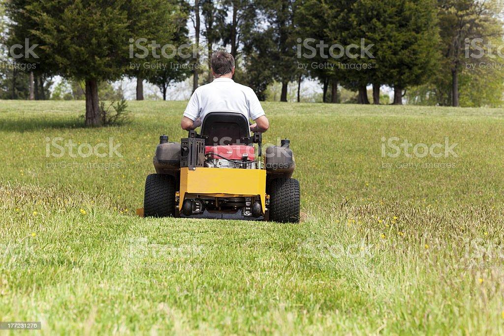 Senior man rides zero turn lawn mower on turf royalty-free stock photo