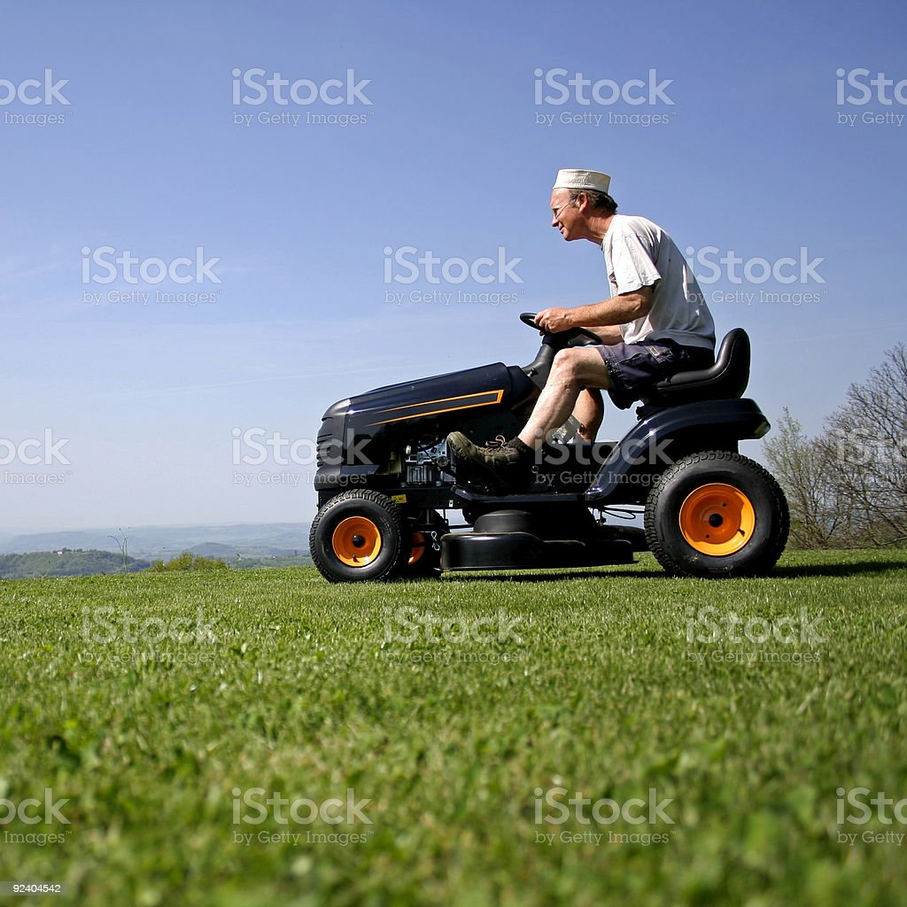 Senior man riding a mower on grass stock photo