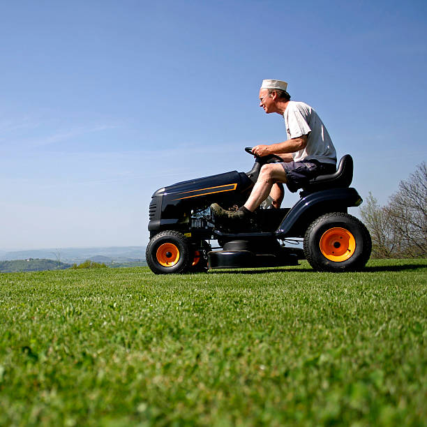 senior man riding a mower on grass - riding lawn mower stock photos and pictures