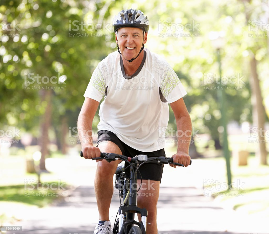 Senior man riding bike in park on sunny day stock photo