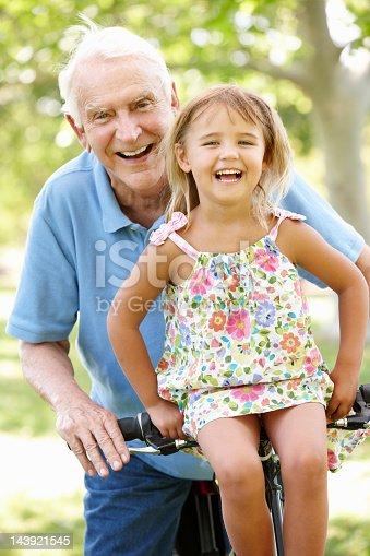 istock Senior man riding bike with granddaughter 143921545