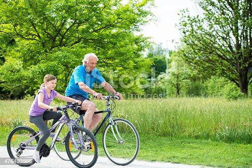 istock Senior Man Riding Bike With Granddaughter 476493566