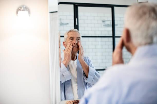 senior woman rieb gesicht beim blick in spiegel - alte spiegel stock-fotos und bilder