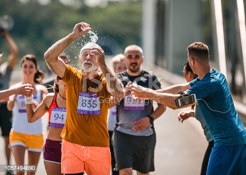 Senior marathon runner refreshing himself with water during a race. There are people in the background.