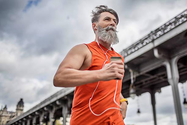 alter mann läuft in der stadt - motivationsmusik stock-fotos und bilder