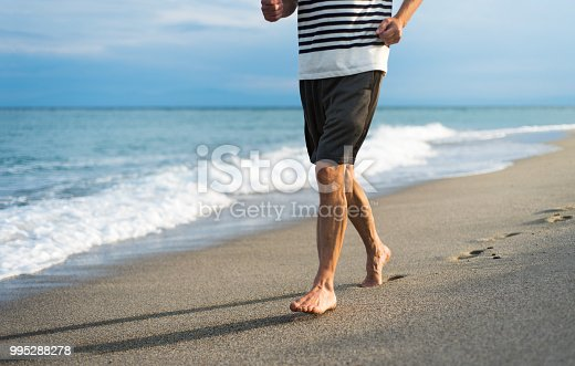 Senior man running on the beach low angle view