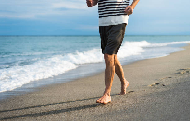 senior man running on the beach - old man feet stock photos and pictures