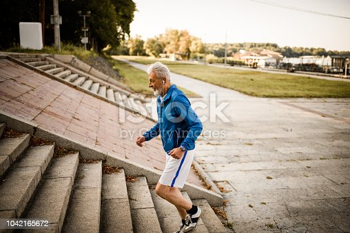 Side view of a senior man running up the stairs
