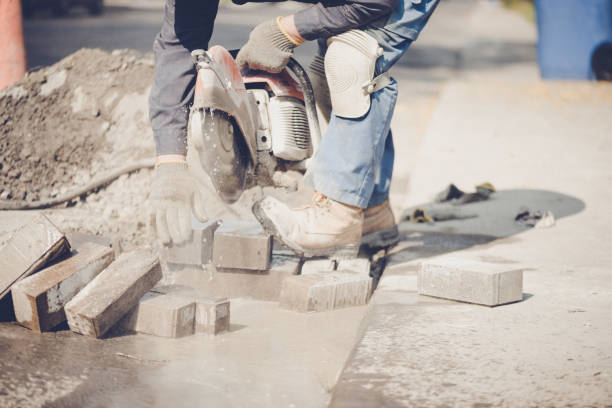 Senior man saw cutting concrete blocks stock photo