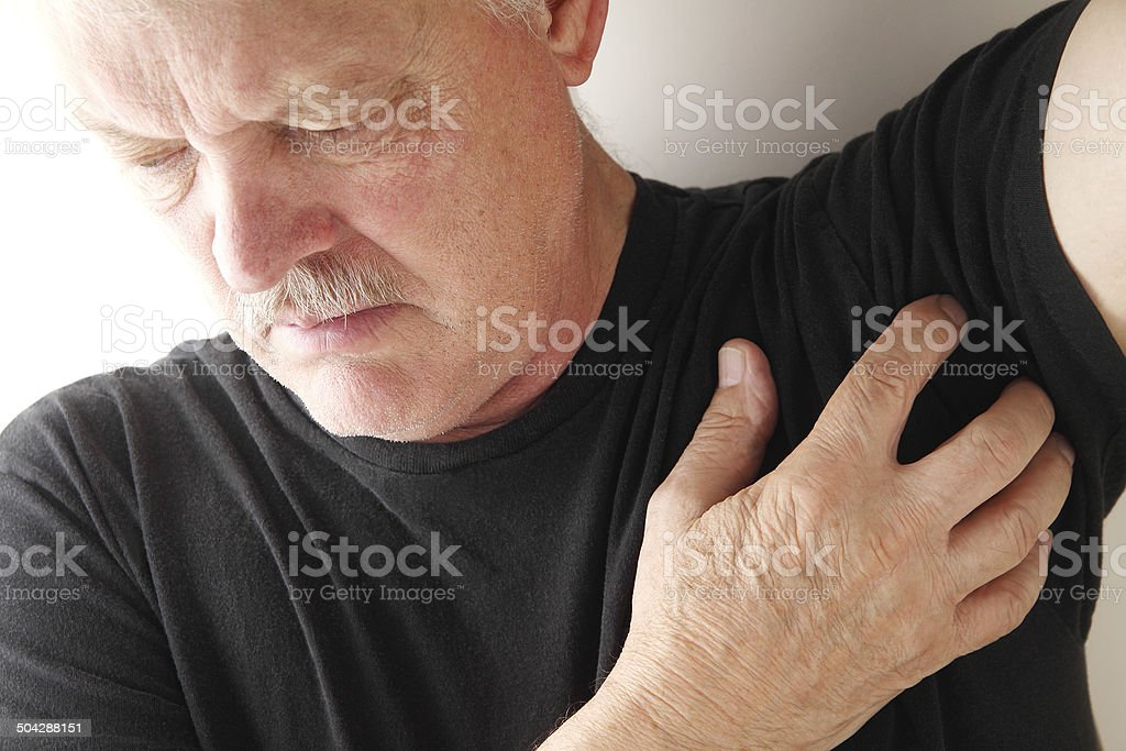 senior man scratches under his arm stock photo