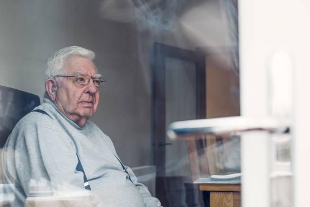 senior man seen through a window - old men window imagens e fotografias de stock