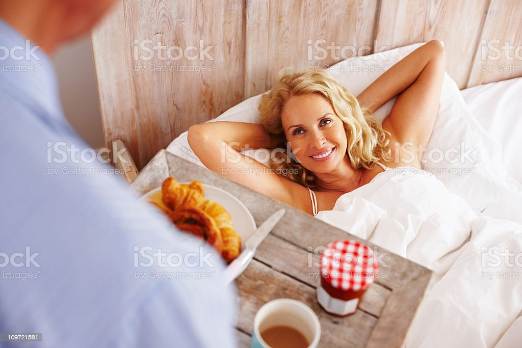 Senior man serving breakfast to a mature woman royalty-free stock photo