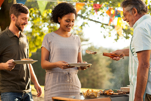 Senior man serving grilled meat to his son and daughter-in-law