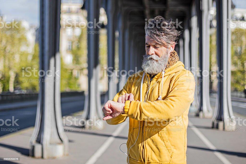 Senior man setting up the smart watch stock photo