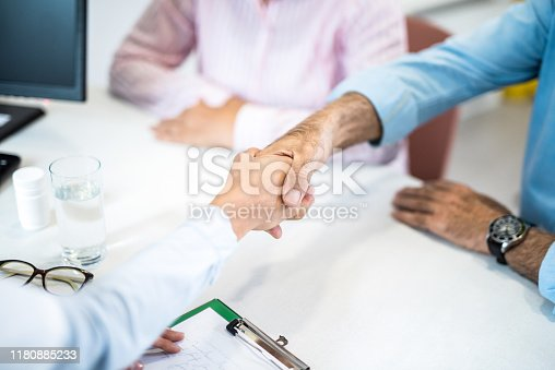 Senior man shaking hands with young female doctor.